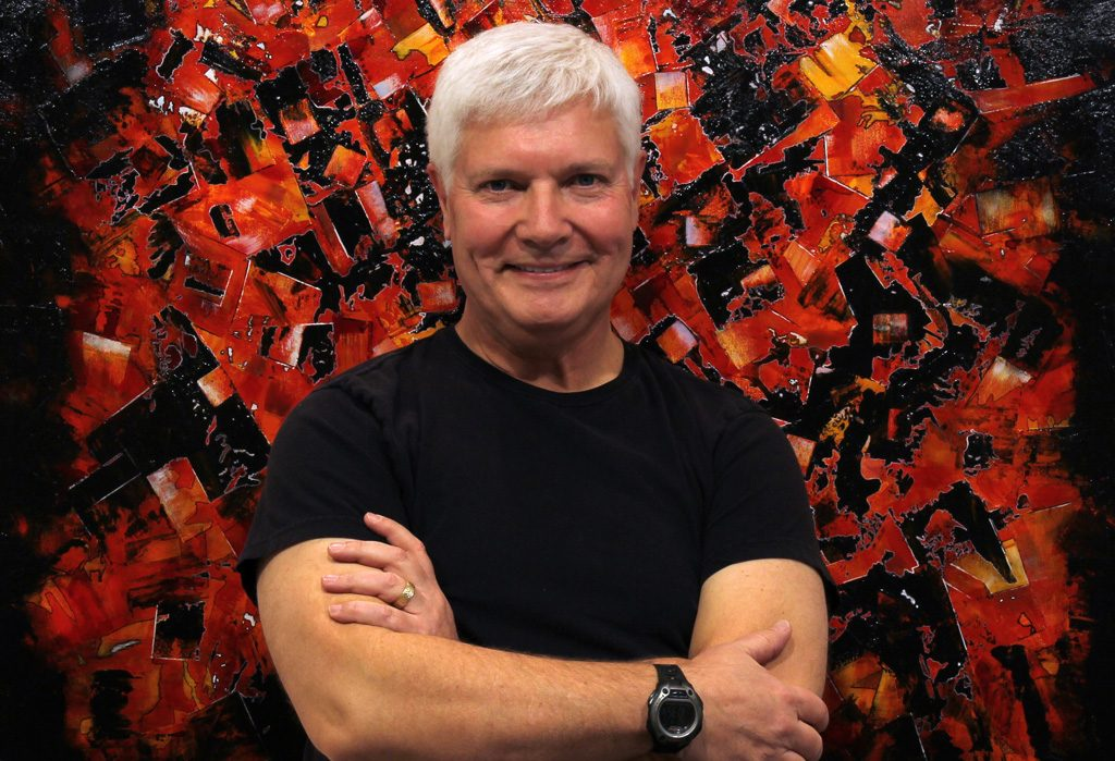 Steve Penner standing in front of vibrant painting